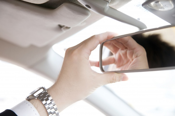 A man reaching up to adjust a rear-view mirror