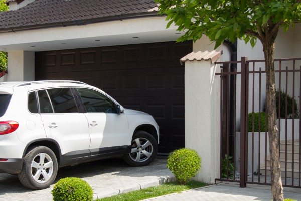 A white SUV entering a home garage
