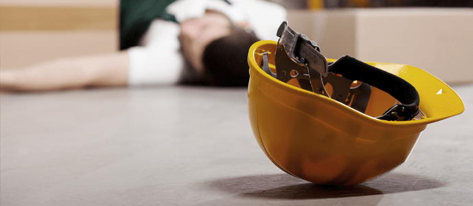 An industrial worker lies injured at work