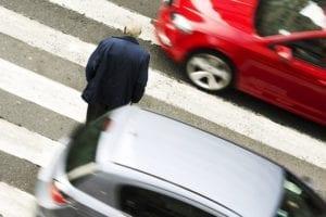 An elderly man walks across a street in heavy traffic