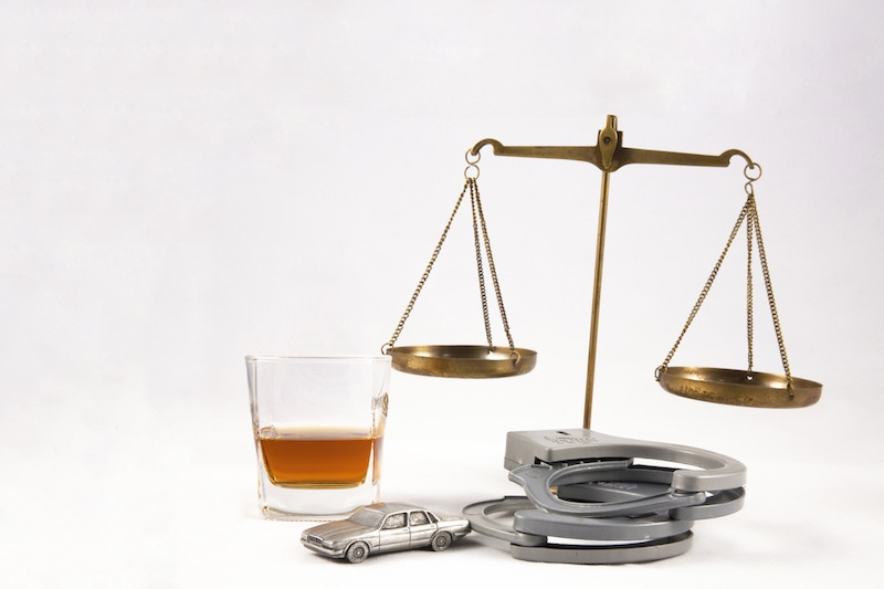 The scales of justice behind a glass of whiskey, a pair of handcuffs and a metal car