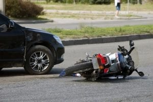 Después de un accidente, una motocicleta yace en la calle junto a un automóvil dañado