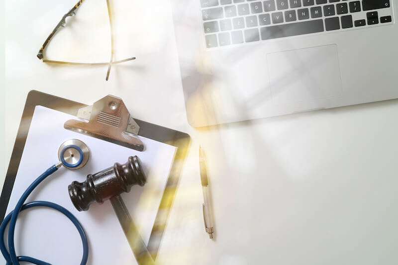 A stethoscope and a gavel rest on a notepad next to a laptop on a desk