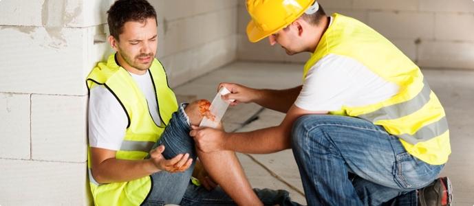 Un hombre ayuda a un compañero de trabajo herido.