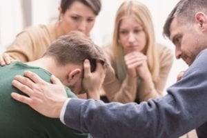Close-up of a devastated young man holding his head in his hands and friends supporting him during group therapy