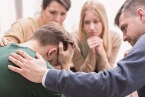 Primer plano de un joven devastado con la cabeza entre las manos y amigos que lo apoyan durante la terapia grupal