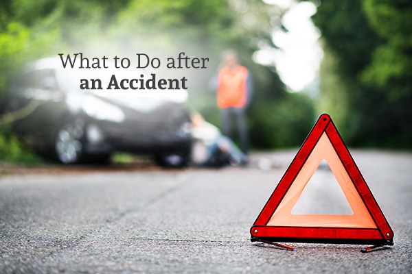 An orange triangular traffic hazard indicator with a car crash in the background with the words what to do after an accident