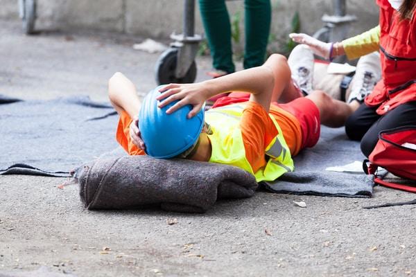 Empleado que recibe primeros auxilios después de un accidente laboral