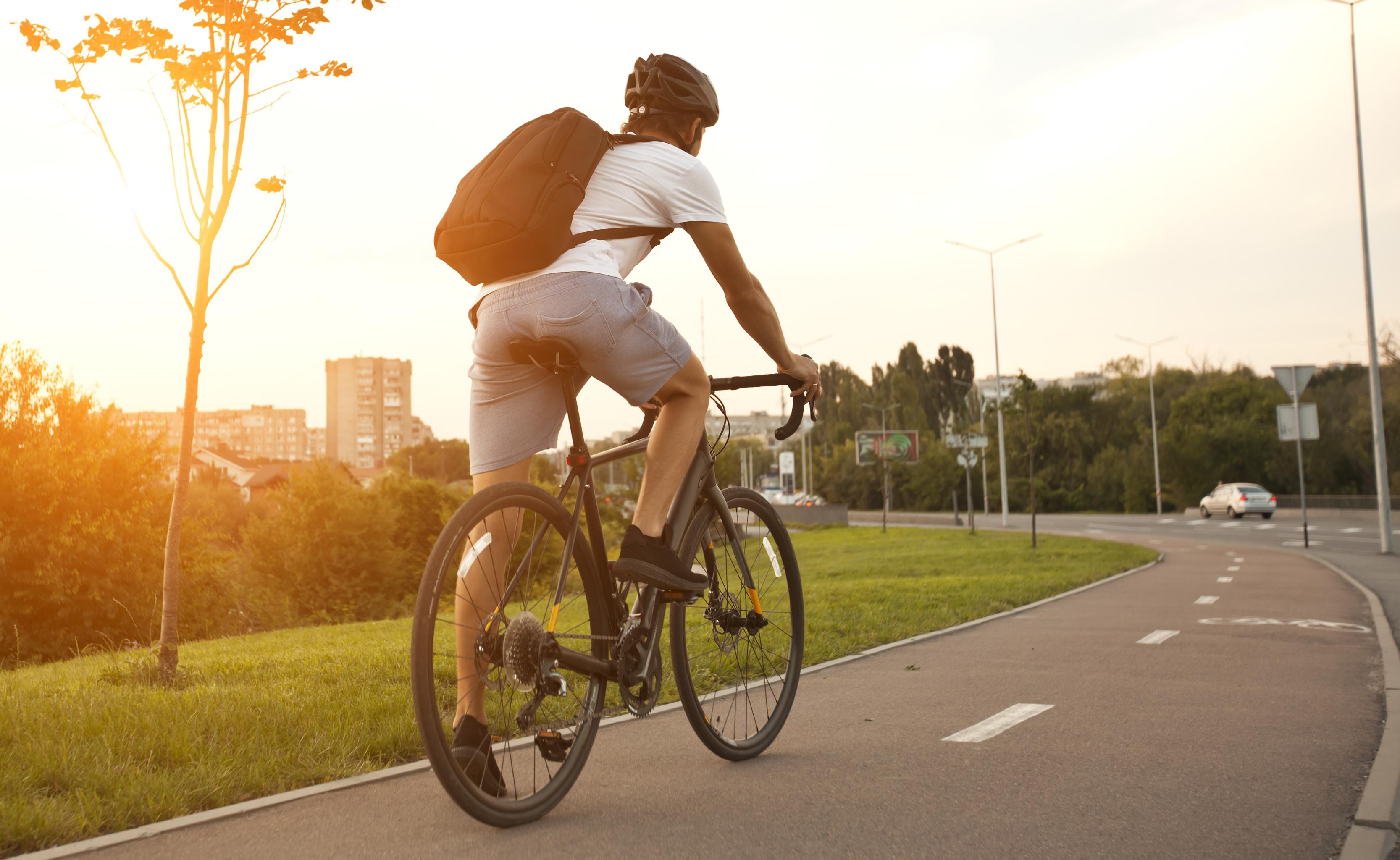 Un chico con ropa casual está yendo en bicicleta por la noche.