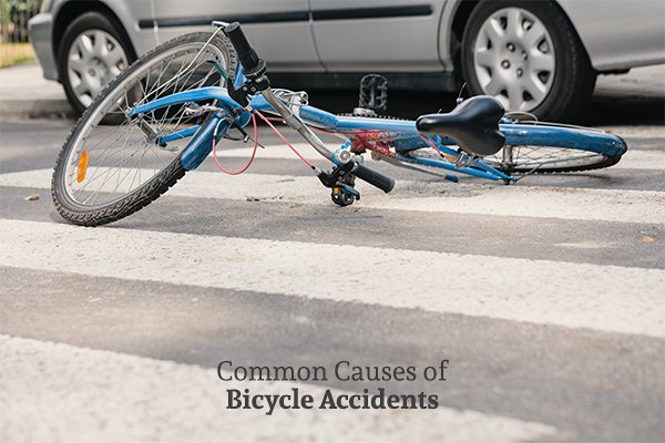 A mangled bike on a crosswalk beside a car above the words common causes of bicycle accidents
