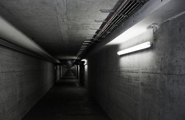 Pasillo mal iluminado que conduce a un estacionamiento