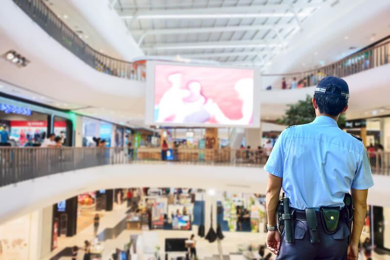 Un guardia de seguridad se encuentra en una posición estratégica para ver tres niveles en un centro comercial.