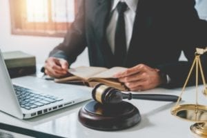 Un abogado sentado en su escritorio con mazo, balanza legal y computadora.