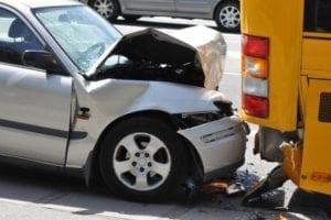 A car has rear-ended a school bus.