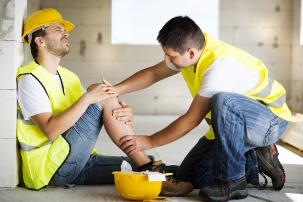 A construction worker is holding his leg in pain and another construction workers is aiding him.