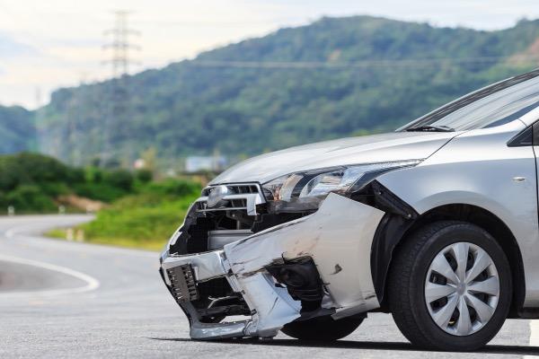 Un automóvil con su parachoques delantero colgando debido a un accidente.