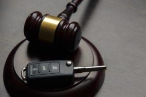 Un martillo está sentado en un escritorio con la llave de un auto.