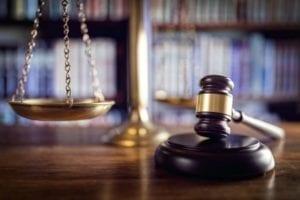 Un mazo en un escritorio con una escala legal.