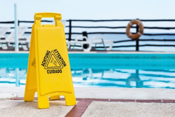 A caution when wet sign sits in front of a pool.