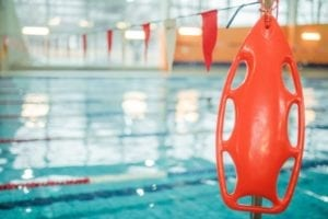 A safety buoy in front of a pool.