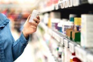 A consumer is checking a warning label on a bottle of pills.