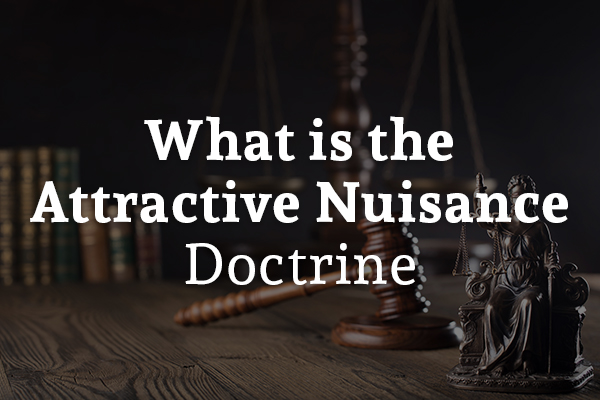 A gavel and a legal scale are sitting on a desk with the words, what is the attractive nuisance doctrine.