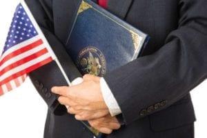 Un hombre sostiene una bandera estadounidense y un nuevo paquete de ciudadanía.