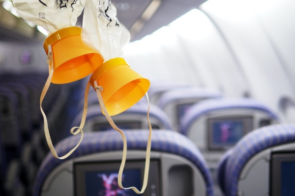 A pair of oxygen masks coming down from the storage compartment in an airplane.