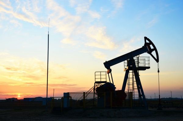 A picture of a sunrise over an oilfield.