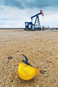 Un casco de seguridad frente a un campo petrolero.