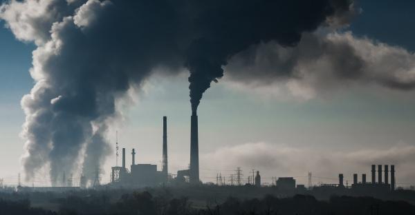 Una imagen de una planta química con humo saliendo de las chimeneas.