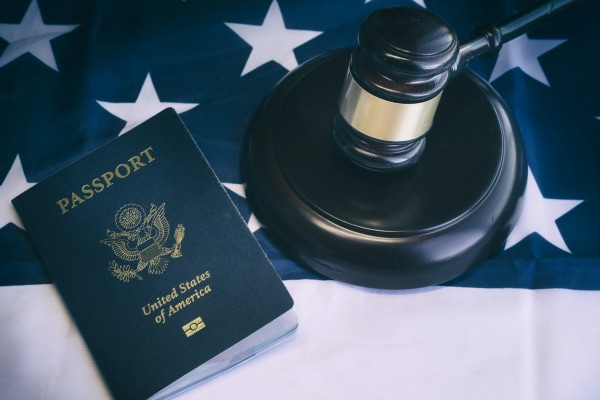A passport, a gavel, and an American Flag.