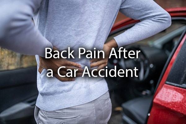 A person holding their back in pain after a car accident with the words, back pain after a car accident.