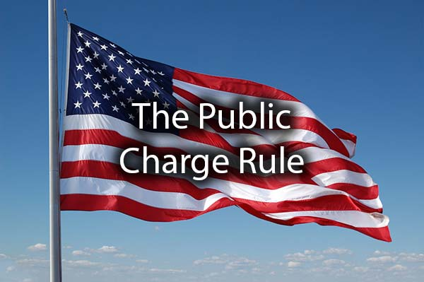 An American Flag with the words, the public charge rule.