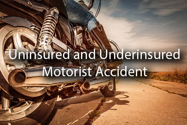 A motorcycle on the road with the words, uninsured and underinsured motorist accident.